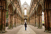 BAW, Jedburgh Abbey view from inside with woman walking up aisle, red brick coloumns and arches with mould and aged, grey sky