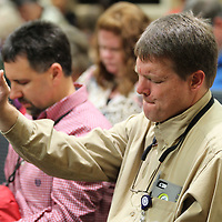Greg napier raises his hand to agree with the closing prayer during Thursday's National Day of Prayer gathering held at City hall in Tupelo.
