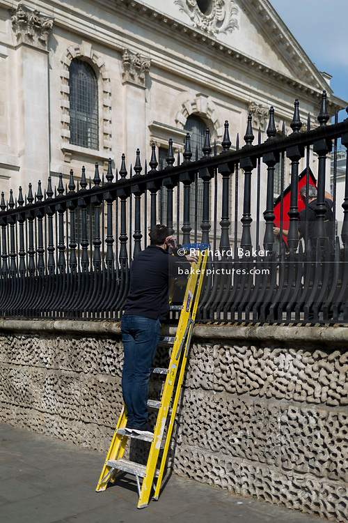 While a workmate manhandles a red panel, a workman pauses up yellow lassers at the rear St. Martin-in-the-Fields church off Trafalgar Square, on 30th April 2019, in London, England