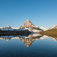 sunrise and reflectioin on two medicine lake, glacier national park, montana