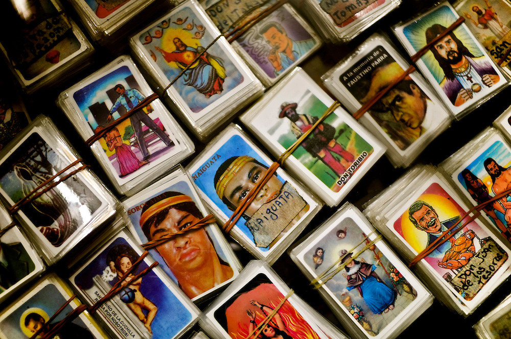 "Assorted cards of saints and deities for sale in a shop outside of the Quibayo base camp. Followers place the cards on the alters that they construct in Sorte mountain, make rituals and ask the saints, ranging from indian chiefs to doctors, political leaders such as Simon Bolivar, to deceased ""malandros"" or gangsters to bless areas of their lives, including health, love, finances, etc."