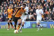 Hull City striker Chuba Akpom (19) held by Luke Murphy (8) during the Sky Bet Championship match between Hull City and Leeds United at the KC Stadium, Kingston upon Hull, England on 23 April 2016. Photo by Ian Lyall.