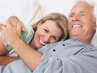 Couple embracing lying in bed