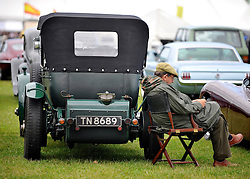 © Licensed to London News Pictures. 17/09/2011. GOODWOOD, UK. A man rests in the carpark. The Goodwood Revival at Goodwood in West Sussex today (17 September 2011). The revival is the world's largest historic motor race meeting, which relieves the 'glorious' days of the race circuit. Competitors and enthusiasts all dress in period fashion to enhance the experience. Photo credit : Stephen Simpson/LNP