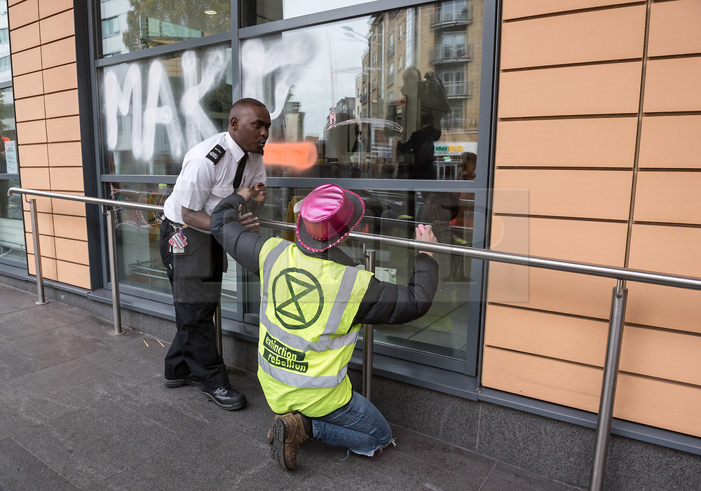 © Licensed to London News Pictures. 08/10/2018. Bristol, UK. 'Extinction Rebellion' campaign event 'Make Ecocide Law' about the threat of climate change, at Bristol Magistrates Court and Marlborough Street. The campaign wants to make ecocide a crime in UK law, saying the threat of climate change threatens the lives of millions of people on the planet. The campaign is organised by Rising Up, and the event happened on the day that the Intergovernmental Panel on Climate Change (IPCC) has issued a special report on the impact of global warming of 1.5C. Campaigners used removable chalk spray to write on the windows of Bristol Magistrates Court, and blocked the main road before being removed by police. There were three arrests. Rising Up plans more actions in November. Photo credit: Simon Chapman/LNP