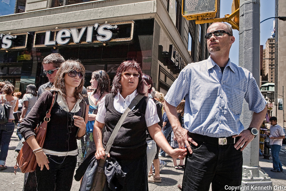 A tourist Family on the corner of 43rd Street and 7th Avenue in Times Square in New York City.