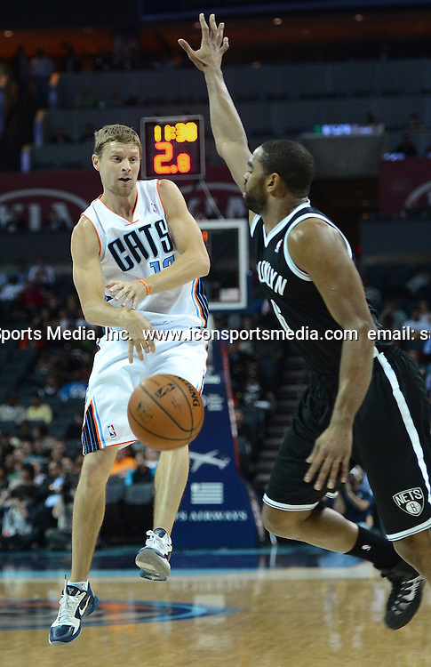 March 26, 2014 - Charlotte, NC, USA - The Charlotte Bobcats' Luke Ridnour, left, passes the ball as the Brooklyn Nets' Alan Anderson defends in the first half on Wednesday, March 26, 2014, at Time Warner Cable Arena in Charlotte, N,C. The Bobcats won in overtime, 116-111