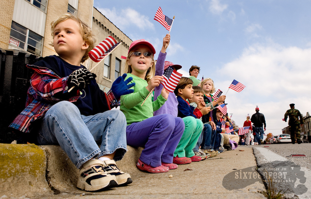 Photo by Gary Cosby Jr.  Kids line the curb with flags and wave during the annual Veteran's Day Parade along Bank Street in Decatur. From left are Olsen Howard, Sophie Batchelor, Audrey Batchelor Oliver Howard, Mose Batchelor and Rivers Barran.