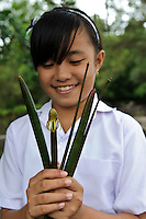 A young girl with mangrove propagules during an environmental education class, Dudepo, Bolmong Selatan, Sulawesi, Indonesia.