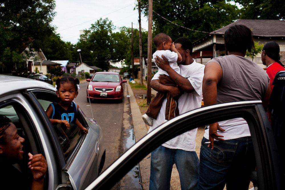 "Sean Williams (middle) picks up a toddler in front of Hoover's Convenience Store and Laundromat while hanging out with other residents in the Baptist Town neighborhood of Greenwood, Mississippi on Thursday, May 20, 2010. Sean wears a shirt that says BAPTIST TOWN in large bold letters on the front and on the back lists the names of imprisoned friends from the neighborhood. Despite its problems, people who come from Baptist Town are proud of their roots, the young men often getting ""B"" and ""T"" tattoos on their forearms."