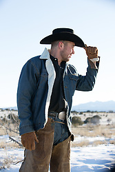 cowboy in chaps outdoors on a snowy mountain range