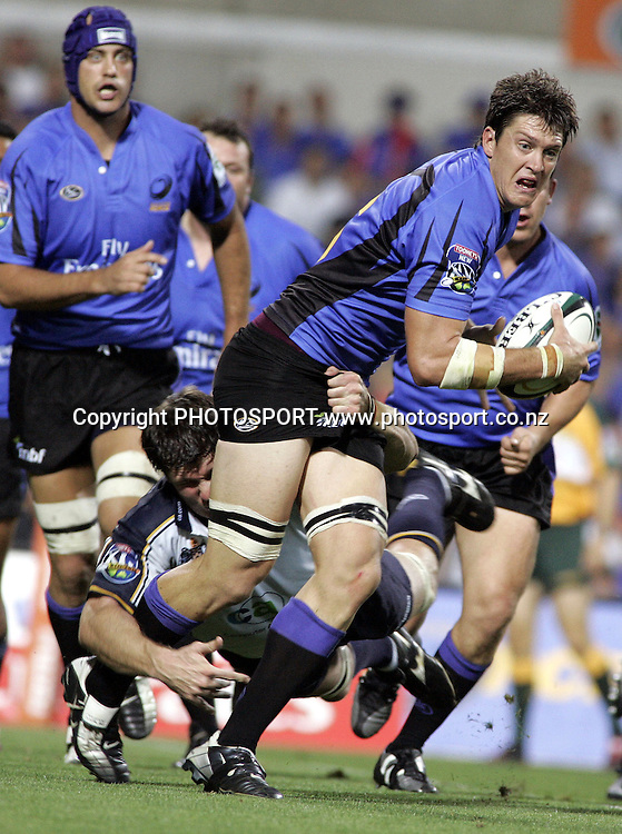 Luke Doherty, Force's Flanker, watched on by his captain Nathan Sharp while being tackled during the opening round of the 2006 Super 14 rugby union match between the Western Force and ACT Brumbies at Subiaco Oval, Perth, Western Australia, on Friday 10 February, 2006.  Final score was Western Force 10 - AC Brumbies 25.  Photo: Christian Sprogoe/PHOTOSPORT