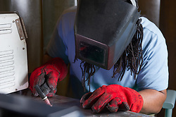 A prisoner welding in a prison workshop making prison beds in HMP Feathstone