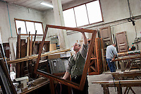 GUIDONIA, ITALY - 7 MARCH 2013: Daniele, a 38 years old polish worker, moves a wooden window after assembling it at the Temeca woodworking shop in Guidonia, Italy, on March 7, 2013. Daniele has been working at the Temeca woodworking shop for 6 years. The Temeca woodworking shop was founded in 1959 by Renzo Tedeschi, 84, father of the current owner Emanuele Tedeschi. Until the 80's the Temeca woodworking shop had 16 employees; after the shop to Emanuele, Renzo's son, four employees retired and the number of the carpenters was reduced to 12.  After the 2009 crisis, the number of workers at the Temeca woodworking were reduced to 7..Gianni Cipriano for The International Herald Tribune