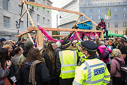 London, UK. 7 October, 2019. Metropolitan Police officers observe climate activists from Extinction Rebellion building a wooden structure as they block Millbank at one end of Lambeth bridge on the first day of International Rebellion protests to demand a government declaration of a climate and ecological emergency, a commitment to halting biodiversity loss and net zero carbon emissions by 2025 and for the government to create and be led by the decisions of a Citizens' Assembly on climate and ecological justice.