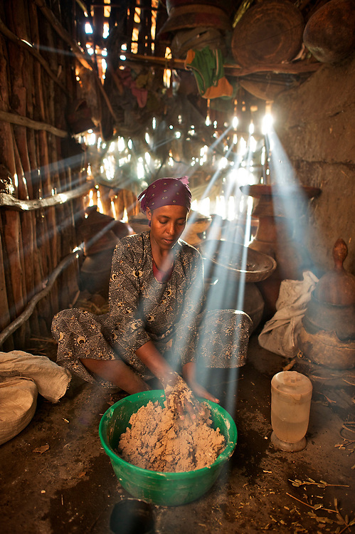 Tayitis Mohammed mixes injera out of teff flower and water in her house in Fontanina near Kombulcha in the Wollo region of the Ethiopian highlands. Injera is the staple bread of Ethiopia, which makes teff a valuable grain. Smoke from the kitchen fire made the rays of the setting sun show up brightly in the dark cookng area to the side of the main room of the stick and clay built house. The walls of the house are caulked with teff straw as well.<br /> <br /> The injera batter, a bit runny like pancake batter, is then transfer to the bucket last used to &quot;ferment&quot; the injera for a couple of days, picking up the residual yeasts in the bucket and providing leavening to the bread.<br /> <br /> Contact: Genene Gezu<br /> Program Coordinator<br /> Ethio-Organic Seed Action (EOSA)<br /> Tel: +251 11 550 22 88<br /> Mobile: +251 91 1 79 56 22<br /> genenegezu@yahoo.com<br /> shigenene@gmail.com<br /> PO Box 5512<br /> Addis Aababa, Ethiopia