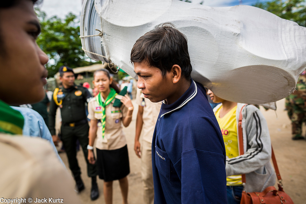 16 JUNE 2014 - POIPET, CAMBODIA: A Cambodian migrant returning to Cambodia carries his belongings through Poipet, Cambodia. More than 150,000 Cambodian migrant workers and their families have left Thailand since June 12. The exodus started when rumors circulated in the Cambodian migrant community that the Thai junta was going to crack down on undocumented workers. About 40,000 Cambodians were expected to return to Cambodia today. The mass exodus has stressed resources on both sides of the Thai/Cambodian border. The Cambodian town of Poipet has been over run with returning migrants. On the Thai side, in Aranyaprathet, the bus and train station has been flooded with Cambodians taking all of their possessions back to Cambodia.  PHOTO BY JACK KURTZ