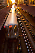 "Sunrise illuminates a train in the Chicago rapid transit system known as the""L""  in Chicago, IL, USA."