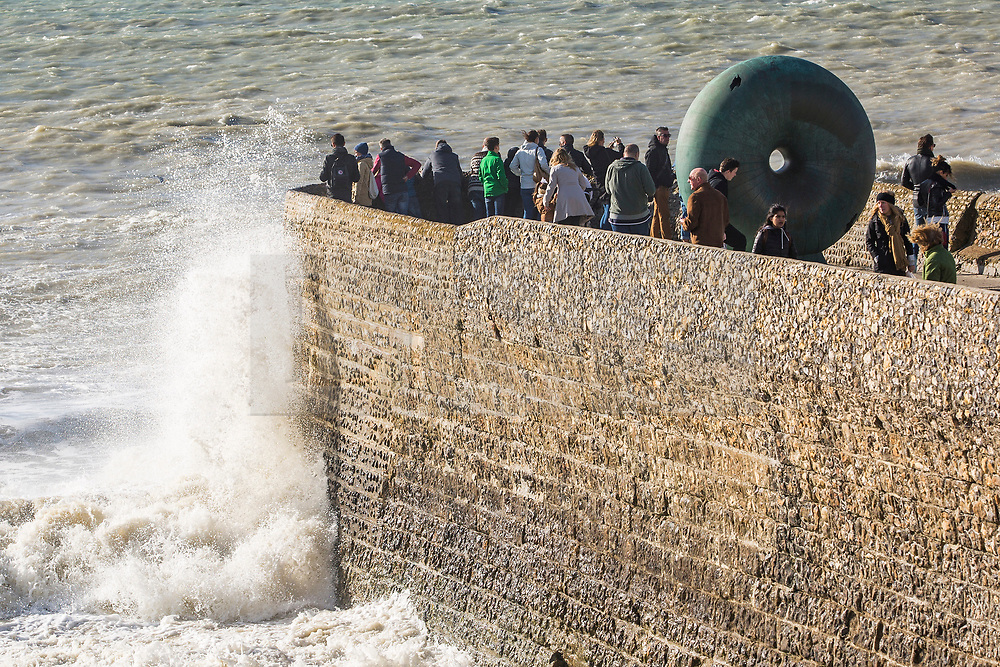 © Licensed to London News Pictures. 22/10/2017. Brighton, UK. Members of the public watch the powerful waves crash in to the pontoon on Brighton and Hove seafront. Photo credit: Hugo Michiels/LNP