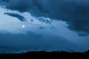 The full moon shines between layers of storm clouds that are developing over Mount Adams, a volcano in Washington state. Mount Adams, at 12,280 feet (3,743 meters), is the second-tallest mountain in Washington and is still considered potentially active even though it last erupted in 550 BC.
