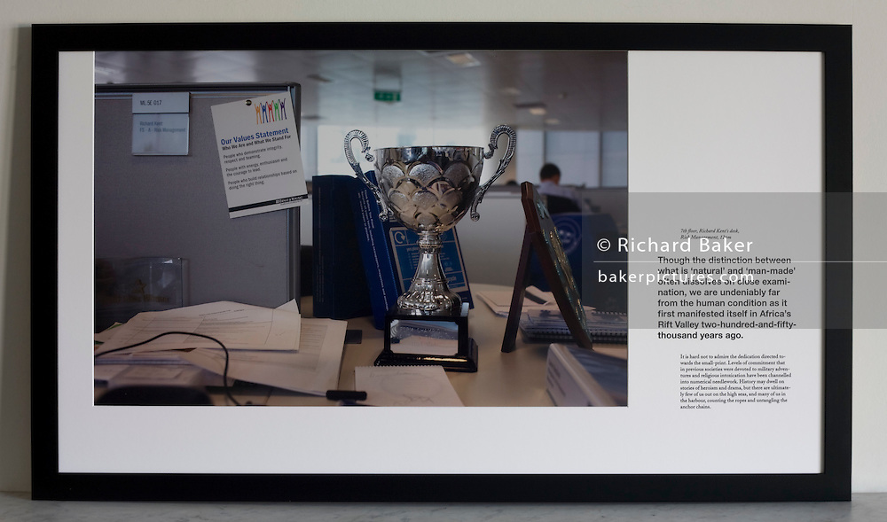 Office worker's cluttered desk with trophy, shield and company statement at an auditing company's London headquarters.<br />
