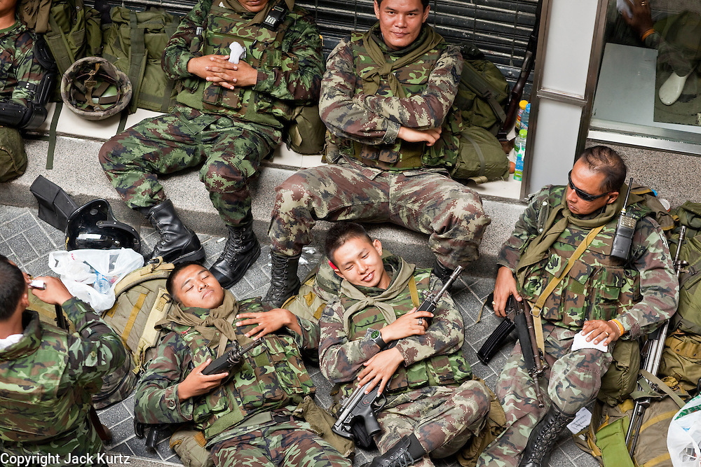 "Apr. 19 2010 - BANGKOK, THAILAND: Thai soldiers relax in front a ""Body Glove"" store in the Silom financial district in Bangkok Monday. Hundreds of Thai soldiers, including reservists and front line units, and riot police moved into the Silom financial district Monday, not far from the red-shirts' main protest rally site, in Ratchaprasong. The heavy show of force is to prevent the Red Shirts from entering the Silom area. Many of soldiers were greeted as heros by workers in the area, who oppose the Red Shirts.   Photo by Jack Kurtz"