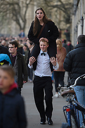 © London News Pictures. 01/05/2016. Oxford, UK. A young man carries a friend on his shoulders as University students and members of the public celebrate May Day in the early hours of the morning near Magdalen Bridge in Oxford, Oxfordshire. This year people were again prevented from jumping from the bridge in to the water due to serious injuries sustained at a previous years event . Photo credit: Ben Cawthra/LNP