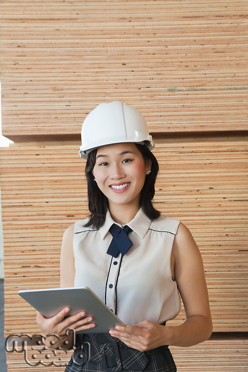 Portrait of young female industrial worker using tablet PC with wooden planks in background