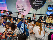 "27 MARCH 2015 - BANGKOK, THAILAND: Shoppers wait for the Style Nanda store to open in ""EmQuartier,"" a new shopping mall in Bangkok. ""EmQuartier"" is across Sukhumvit Rd from Emporium. Both malls have the same corporate owner, The Mall Group, which reportedly spent 20Billion Thai Baht (about $600 million US) on the new mall and renovating the existing Emporium. EmQuartier and Emporium have about 450,000 square meters of retail, several hotels, numerous restaurants, movie theaters and the largest man made waterfall in Southeast Asia. EmQuartier celebrated its grand opening Friday, March 27.    PHOTO BY JACK KURTZ"