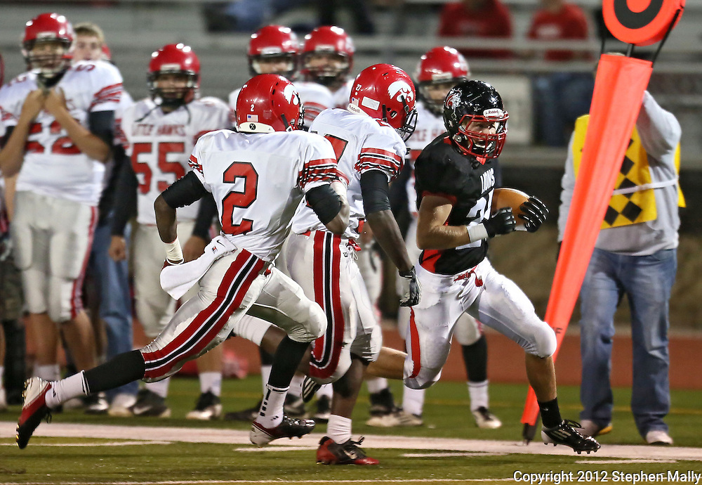 Linn-Mar's Ross Lembeck (25) tries to avoid Iowa City High's De' Airius Salibi (2) and Xavier Washpun (27) on a run down the sidelines during during the game between the Iowa City High Little Hawks and the Linn-Mar Lions at Linn-Mar Stadium in Marion on Friday October 12, 2012.