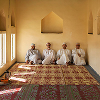 Men waiting for prayer to begin in a sitting area near a mosque in Jabal Akhdar.
