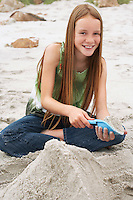 Girl (10-12) playing in sand on beach portrait