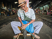 13 MAY 2015 - MAHACHAI, SAMUT SAKHON, THAILAND: A knife sharpener at work on the platform between tracks in the train station in Mahachai) also known as Samut Sakhon, Samut Sakhon province, Thailand.     PHOTO BY JACK KURTZ
