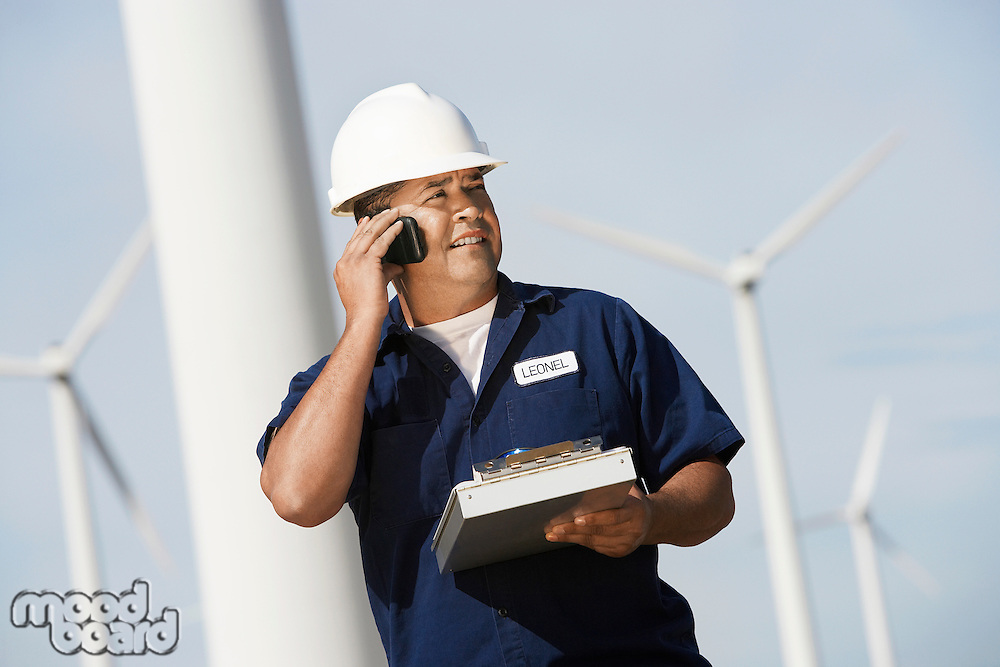 Engineer using mobile phone at wind farm