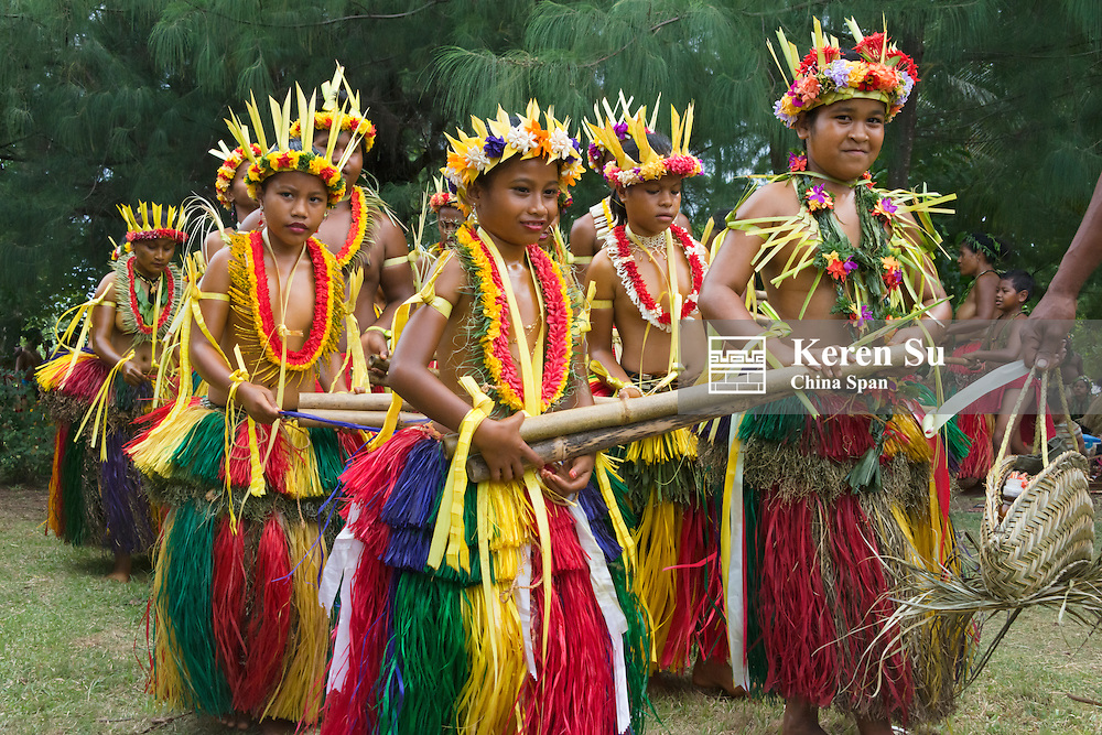 Yapese girls in traditional clothing dancing with bamboo pole at Yap Day Festival, Yap Island, Federated States of Micronesia