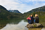 Two women sitting on a boulder in Baranof Lake on Baranof Island scan the opposite side of the lake for wildlife in the Inside Passage of Southeast Alaska.  Tongass National Forest.  Summer.  Morning.  MR.
