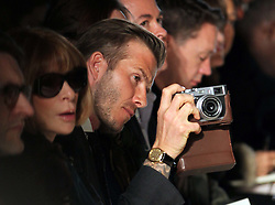 David Beckham takes pictures of the models in the front row at the Victoria Beckham  show at New York Fashion Week AW 2012, Sunday , February 12th 2012.  Photo by: Stephen Lock / i-Images