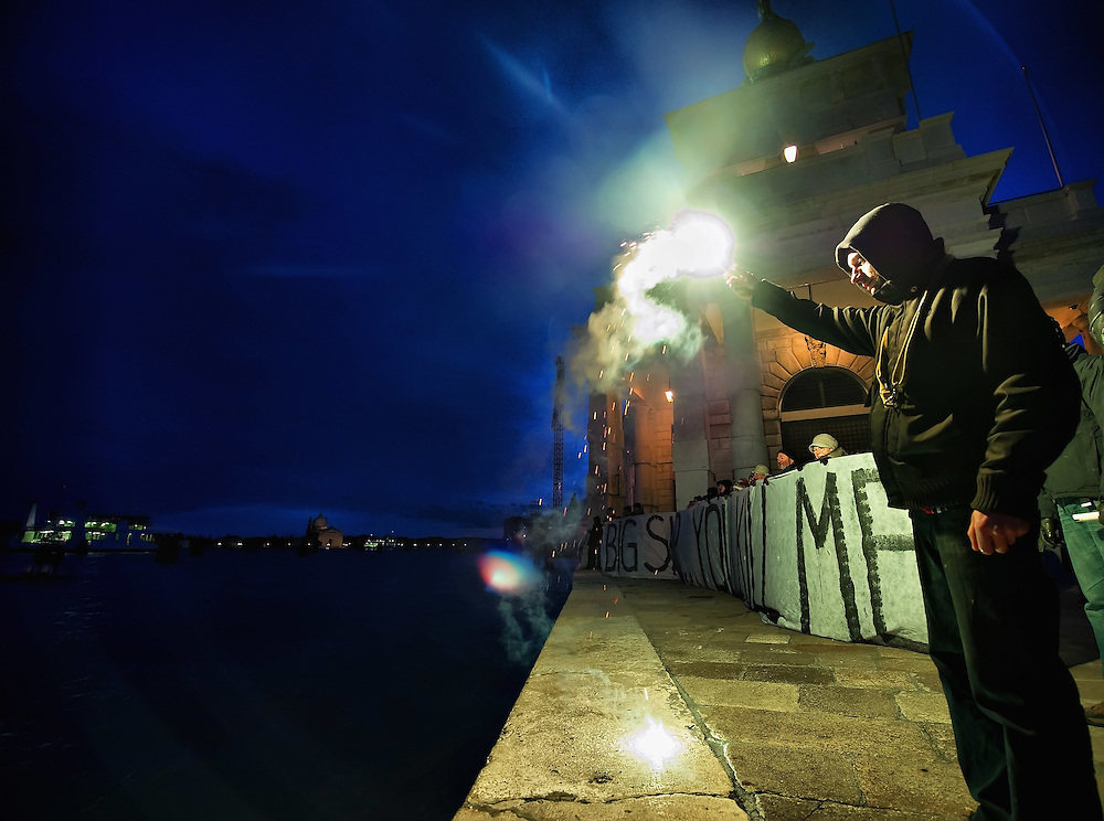 VENICE, ITALY - DECEMBER 18:  A protester holds  a flare in front of a banner as they protest against large cruise ships in St Mark's basin on December 18, 2011 in Venice, Italy. Venetians and Environmentalists are opposed to cruise ships, which plough through the shallow Venetian lagoon, damaging the fragile buildings and canal banks.