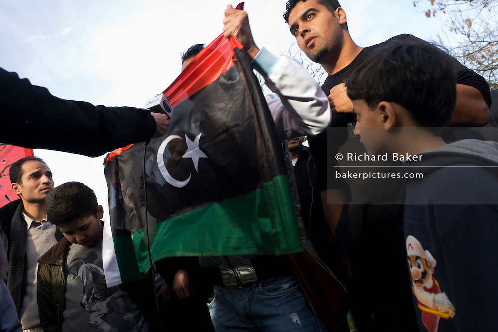 London resident Libyan exiles protest opposite their London embassy against the long-term dictator Muammar al-Gaddafi whose violence has led to a nationwide uprising. Reacting to an interview by an Arabic TV interviewer, a man shows the old Libyan flag now being paraded as an anti Gaddafi symbol. The flag of the independent kingdom was red, black, and green with a crescent and star in the centre. After the Libyan revolution of 1969, the flag was changed to the Arab Liberation Flag of horizontal red, white, and black bands. In 1971 Libya joined the Federation of Arab Republics with Egypt and Syria, which used a similar flag with a hawk emblem in the centre and the name of the country beneath it. When Libya left the Federation in 1977, the new plain green flag was adopted. But during the 2011 uprising, the old flag was once again adopted...