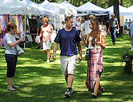 Dave Gates (left) and Aleisha Morosco of New Hope, Pennsylvania walk through the Tinicum Arts Festival which featured about 100 vendors and 180 artists and crafts people Saturday July 11, 2015 in Tinicum, Pennsylvania. (Photo by William Thomas Cain)
