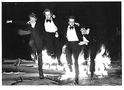 Will Treasure, Nick Rowland, the Rev. Paul Burhold and Paul Sharpe jumping over the traditional burning  boat during the bump supper celebrations in the Oxford University Eights week. Oriel quad, 1981. © Copyright Photograph by Dafydd Jones 66 Stockwell Park Rd. London SW9 0DA Tel 020 7733 0108 www.dafjones.com
