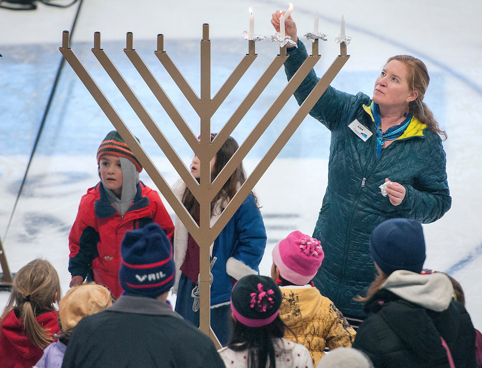 em122716c/metro/Liza Suzanna, director on the Genoviva Chavez Community Center, lights the candles on the menorah on the 4th night of Chanukah. This was during Chanukah on Ice at the Genoviva Chavez Community Center in Santa Fe,  Tuesday December 27, 2016.   (Eddie Moore/Albuquerque Journal)