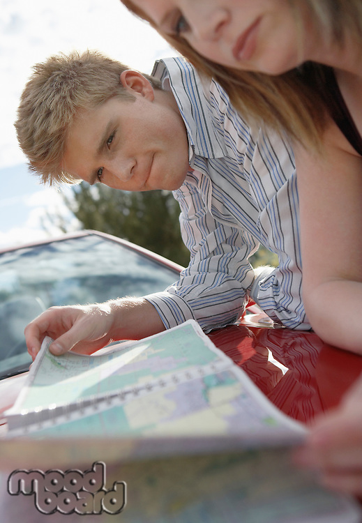 Couple Reading Road Map on Hood of Car