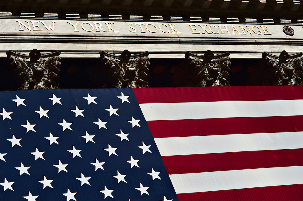 Facade of New York Stock Exchange, showing its name in gold lettering and portion of the giant U.S. flag hanging from columns, New York, New York, U.S., 2008.