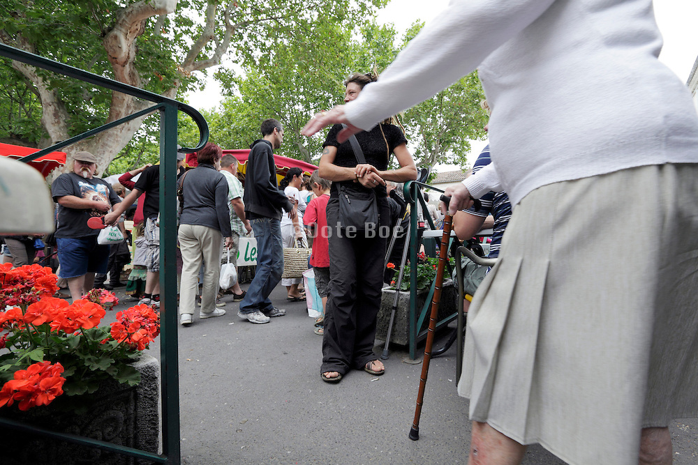 senior woman with walking stick at an outdoors farmers market in South West France