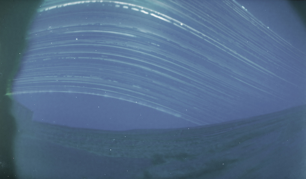 A 6 month long exposure. From winter solstice (lowest arc in the sky) till summer solstice (highest arc). Made with a DIY pinhole camera and a piece of photographic paper.
