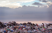 A boy walks through the trash that forms the Cavite City dump about 20 miles south of Manila in the Philippines.  Children and adults who live in the neighboring cemetery hunt daily for recyclable bottles, plastic, metal and the occasional treasure that will help provide the family food and clothing.  About 200 families call Cavite City Cemetery home and most depend on the dump for their income.(Janet Jensen/The News Tribune)