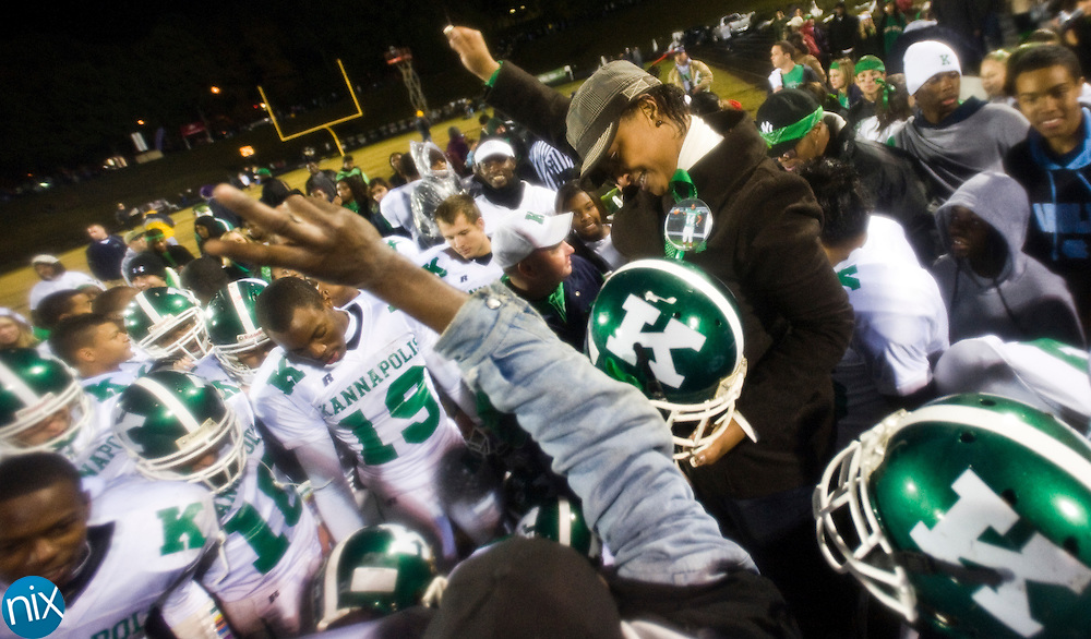 Crystal Willis, the mother of the late Kannapolis football player Dajon Torrence, cheers with the Kannapolis players after the Wonders defeated Concord Friday night at Concord High School. The Wonders won 28-21 to reclaim the bell in the 80th installment of the cross town rivalry known as the Battle of the Bell. (Photo by James Nix)
