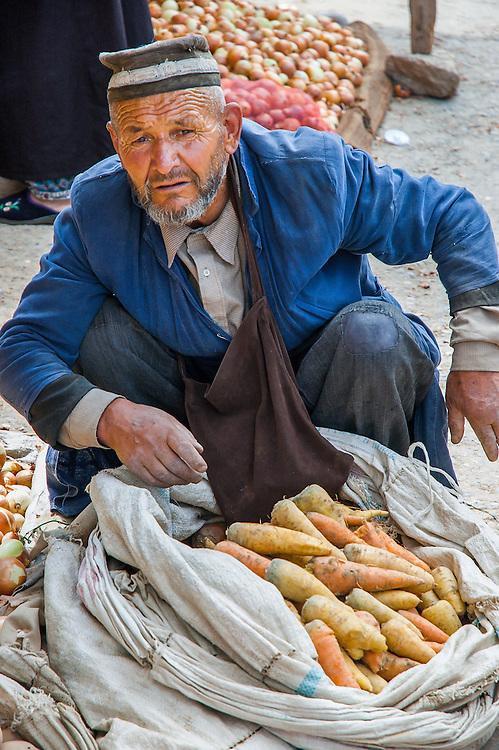 Portrait of an old Tajik man selling carrots, potatoes and onions in a market in western Tajikistan