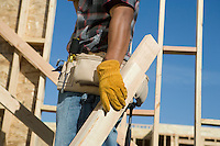 Construction worker carrying planks on construction site